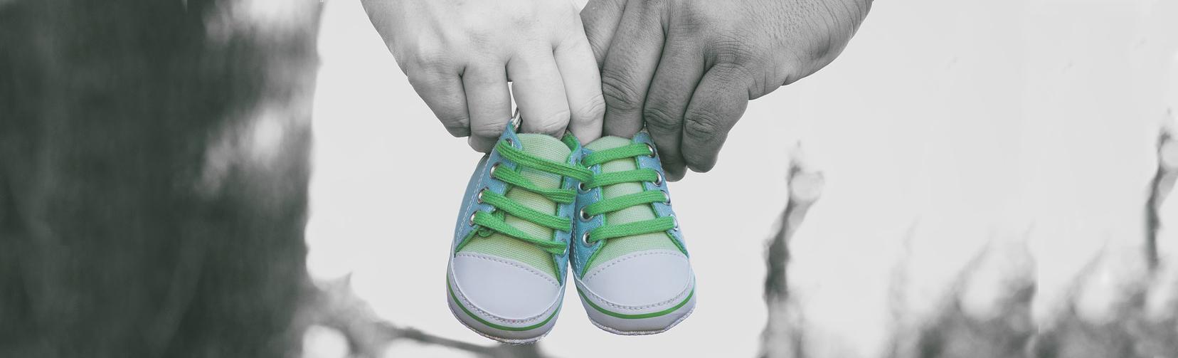Bild eines Paares welches ein Paar Baby Schuhe hält